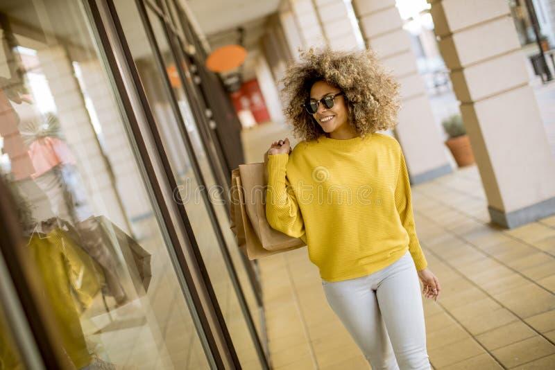 Mujer negra joven con el pelo rizado en compras imágenes de archivo libres de regalías