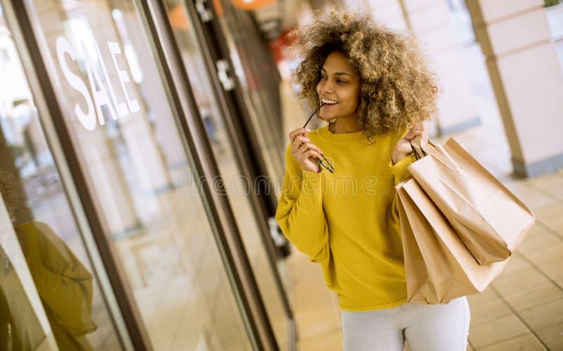 Mujer negra joven con el pelo rizado en compras imagen de archivo libre de regalías