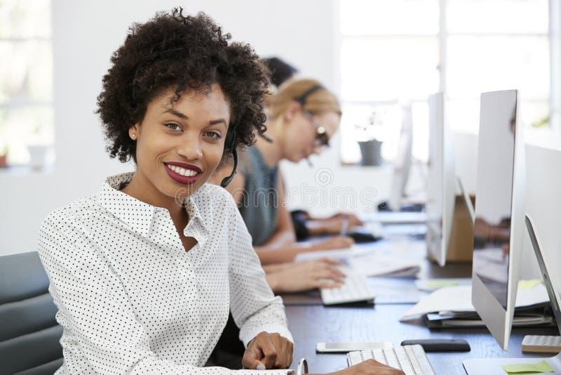 Mujer negra joven con las auriculares que sonríe a la cámara en oficina imagen de archivo libre de regalías