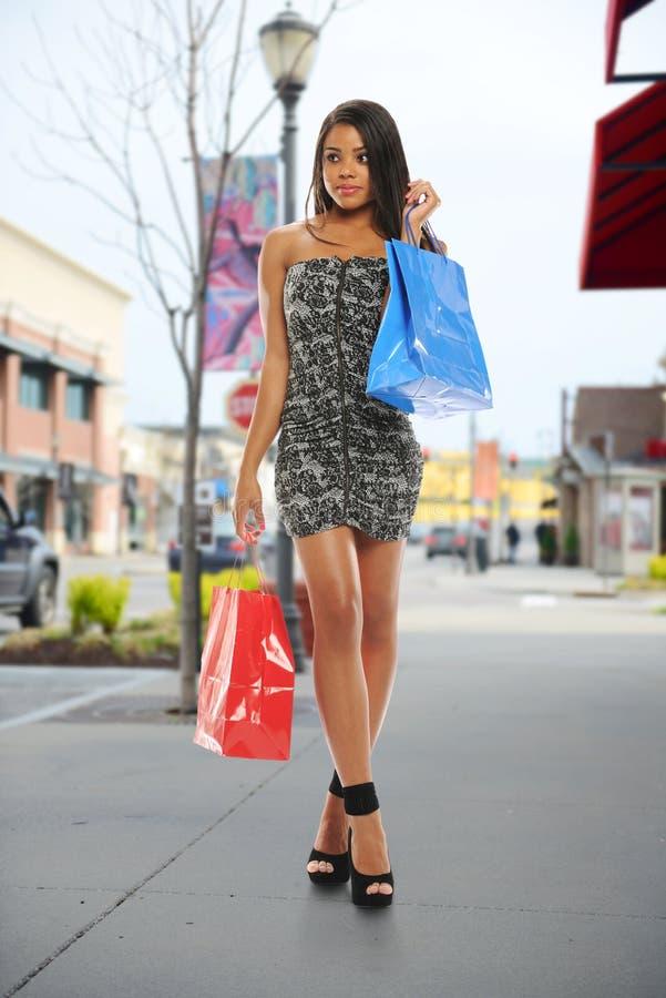 Mujer negra joven con los bolsos de compras fotos de archivo