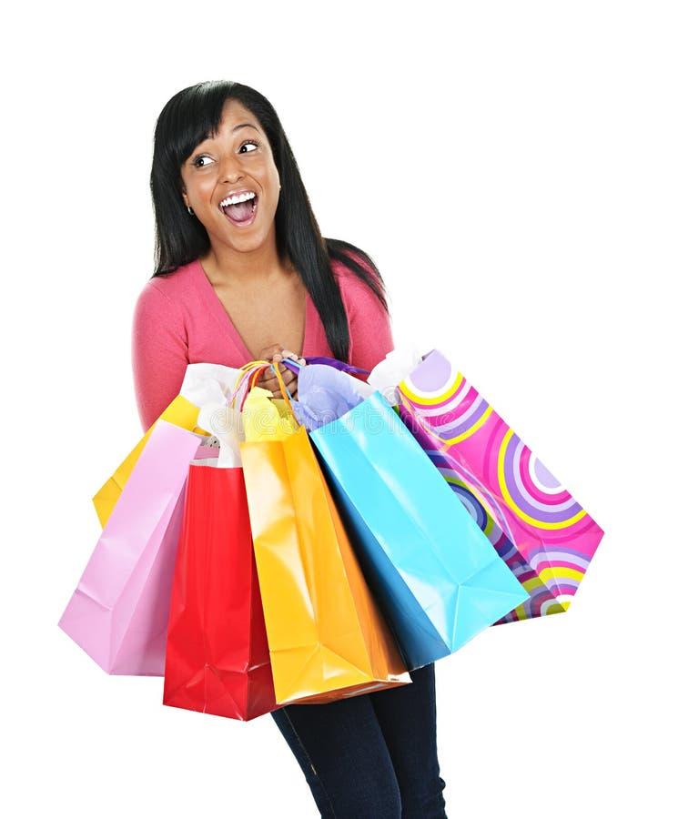 Mujer negra joven emocionada con los bolsos de compras fotografía de archivo libre de regalías