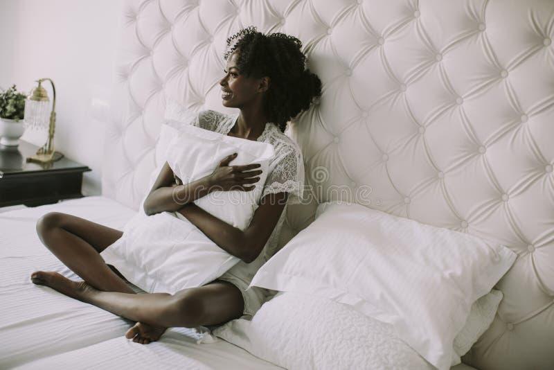 Mujer negra joven en cama fotografía de archivo