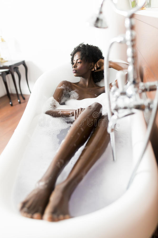 Mujer negra joven en el baño foto de archivo