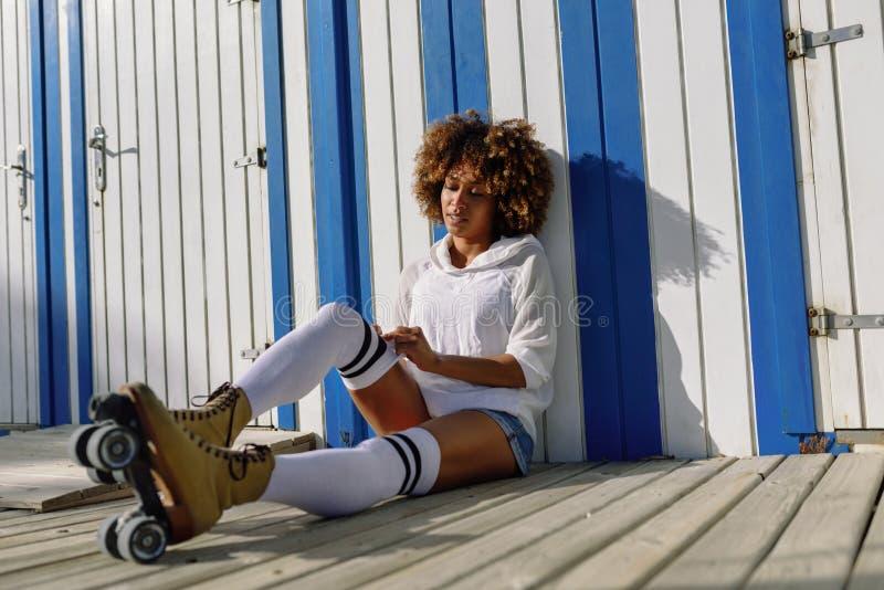 Mujer negra joven en los pcteres de ruedas que se sientan cerca de una choza de la playa fotografía de archivo