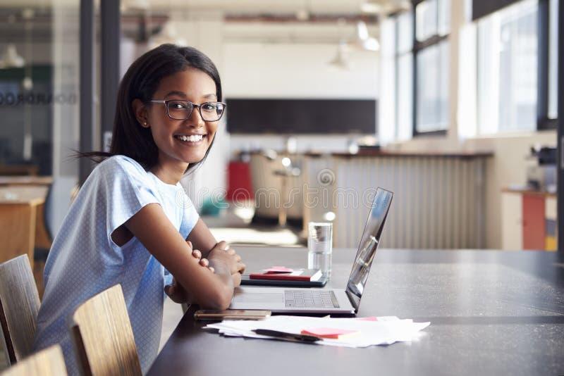 Mujer negra joven en oficina con el ordenador portátil que sonríe a la cámara imagen de archivo