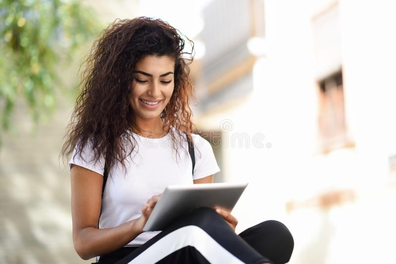 Mujer negra joven en ropa de deportes usando la tableta digital al aire libre fotografía de archivo
