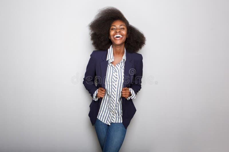 Mujer negra joven feliz con la chaqueta contra fondo gris fotos de archivo