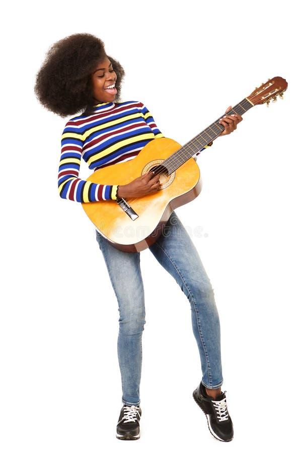 Mujer negra joven feliz del cuerpo completo que toca la guitarra acústica contra fondo blanco aislado imagen de archivo
