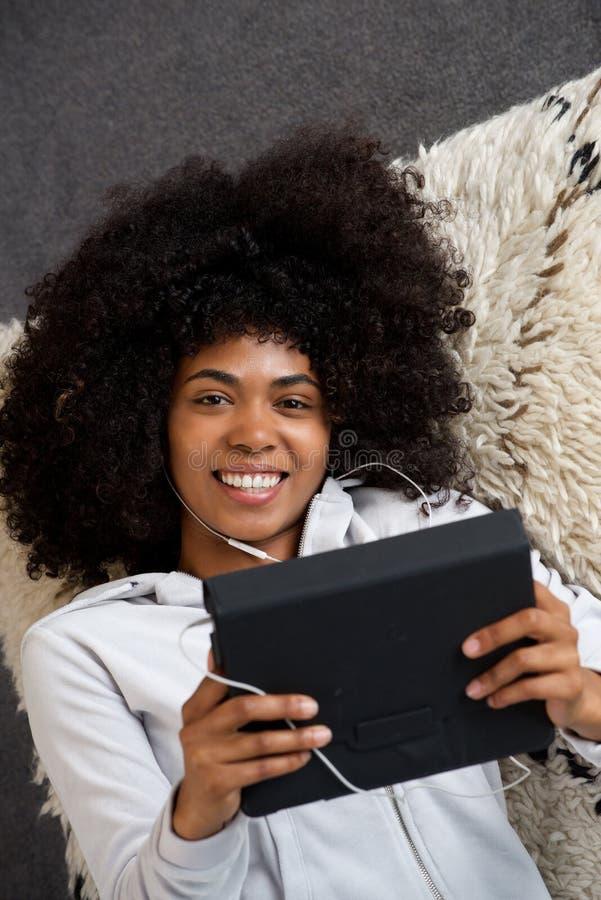 Mujer negra joven hermosa que miente en piso en casa con la tableta digital fotos de archivo libres de regalías