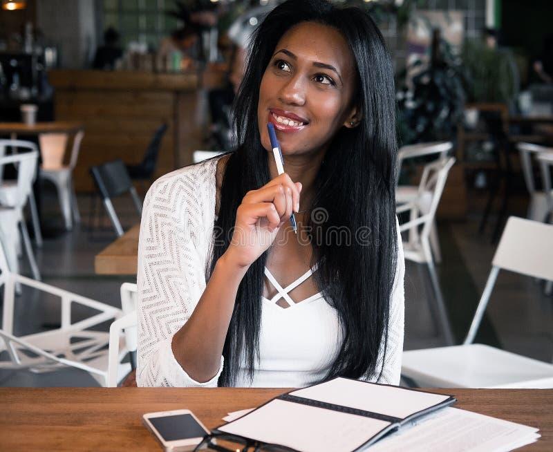 Mujer negra joven hermosa que se sienta en el café y que escribe las notas, concepto de la forma de vida imagen de archivo libre de regalías