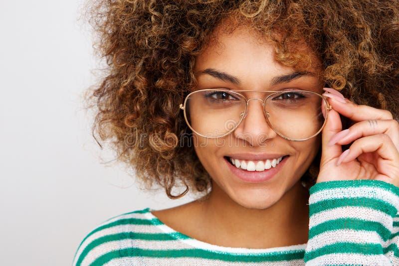Mujer negra joven hermosa que sonríe con los vidrios fotografía de archivo libre de regalías