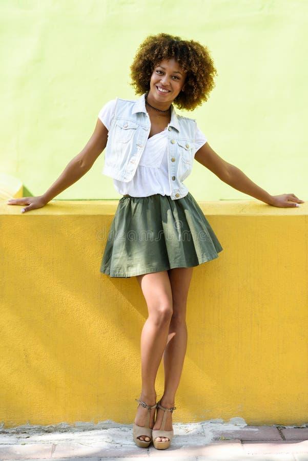 Mujer negra joven, peinado afro, colocándose en fondo urbano fotografía de archivo