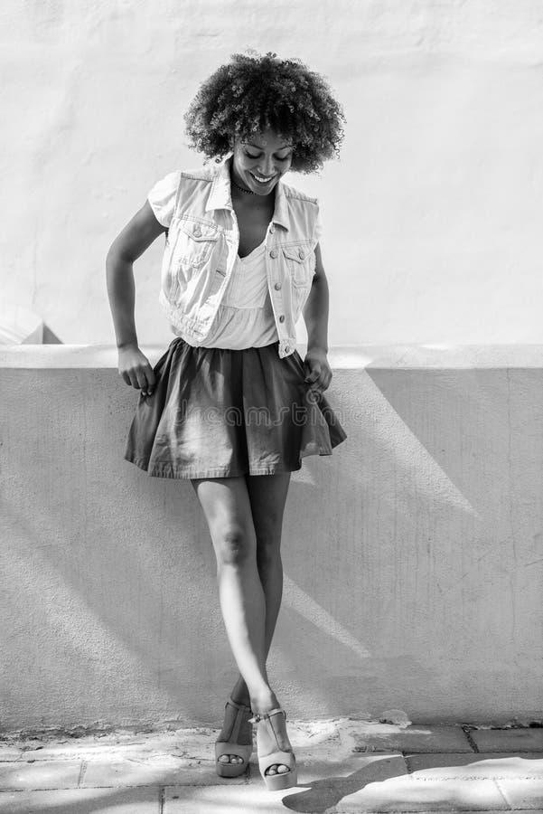 Mujer negra joven, peinado afro, colocándose en fondo urbano imagenes de archivo