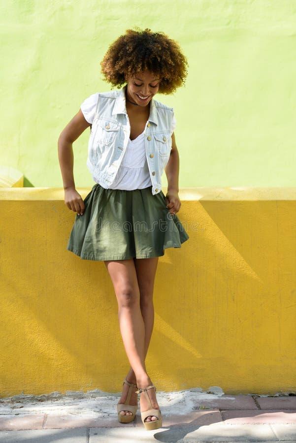 Mujer negra joven, peinado afro, colocándose en fondo urbano imagen de archivo libre de regalías