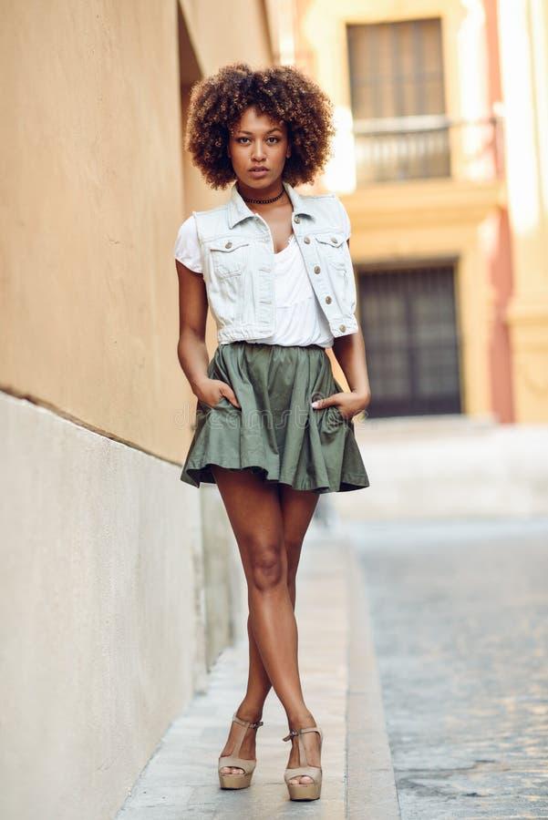 Mujer negra joven, peinado afro, colocándose en la calle Muchacha que lleva la ropa casual en fondo urbano Hembra con la falda, imágenes de archivo libres de regalías
