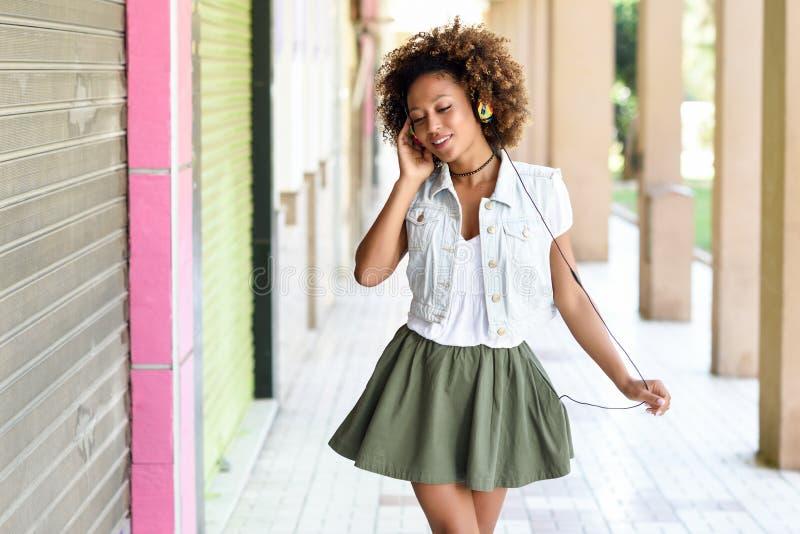 Mujer negra joven, peinado afro, en calle urbana con el headphon foto de archivo