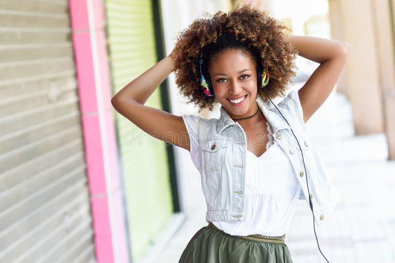 Mujer negra joven, peinado afro, en calle urbana con el headphon imágenes de archivo libres de regalías