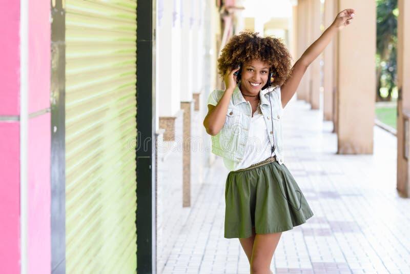 Mujer negra joven, peinado afro, en calle urbana con el headphon imagen de archivo