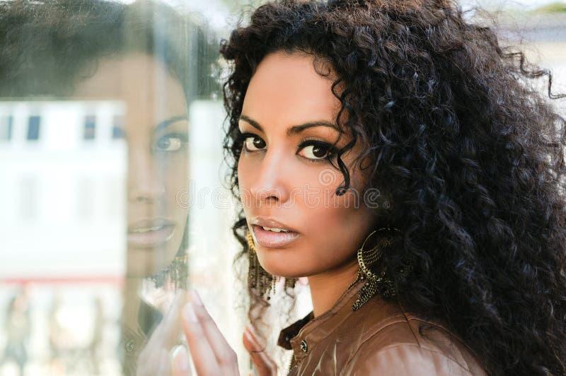 Mujer negra joven, peinado afro, en fondo urbano fotografía de archivo