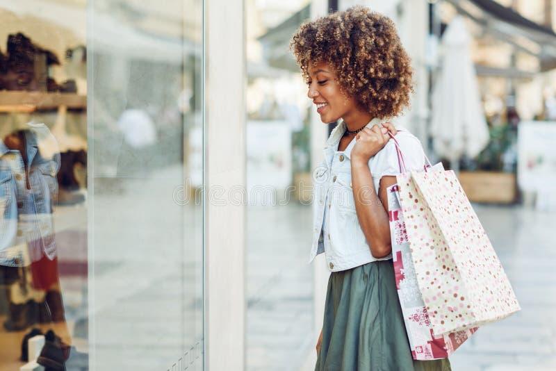 Mujer negra joven, peinado afro, mirando una ventana de la tienda fotos de archivo libres de regalías