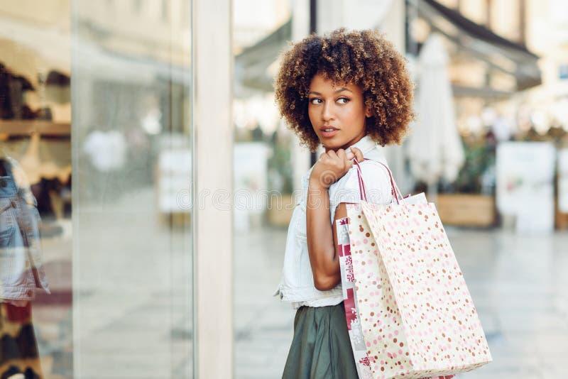 Mujer negra joven, peinado afro, mirando una ventana de la tienda fotos de archivo