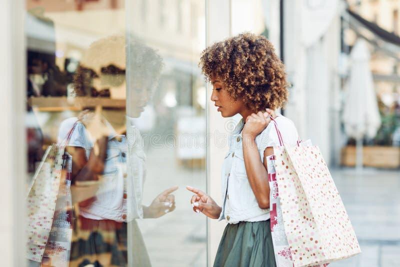 Mujer negra joven, peinado afro, mirando una ventana de la tienda imagen de archivo