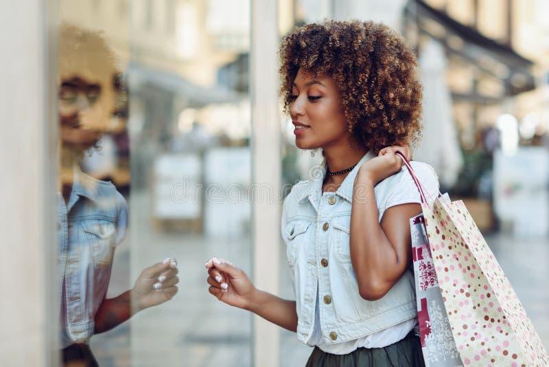Mujer negra joven, peinado afro, mirando una ventana de la tienda imagenes de archivo