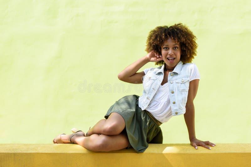 Mujer negra joven, peinado afro, sentándose en una pared urbana fotos de archivo