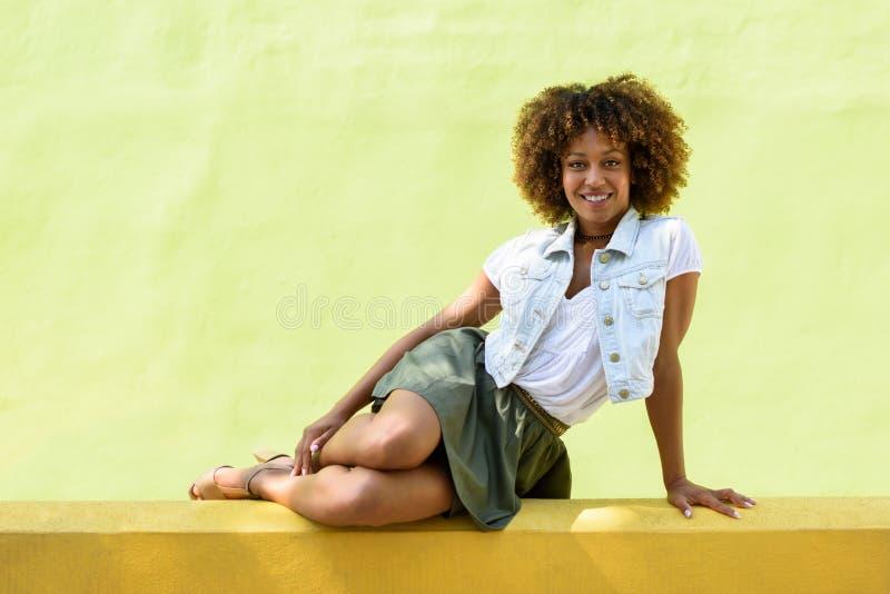 Mujer negra joven, peinado afro, sentándose en una pared urbana fotos de archivo libres de regalías