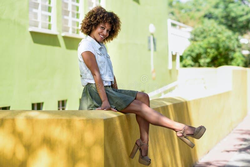 Mujer negra joven, peinado afro, sentándose en una pared urbana imagenes de archivo