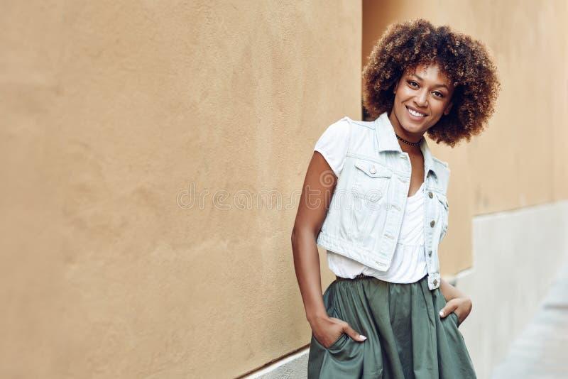 Mujer negra joven, peinado afro, sonriendo en fondo urbano fotografía de archivo libre de regalías