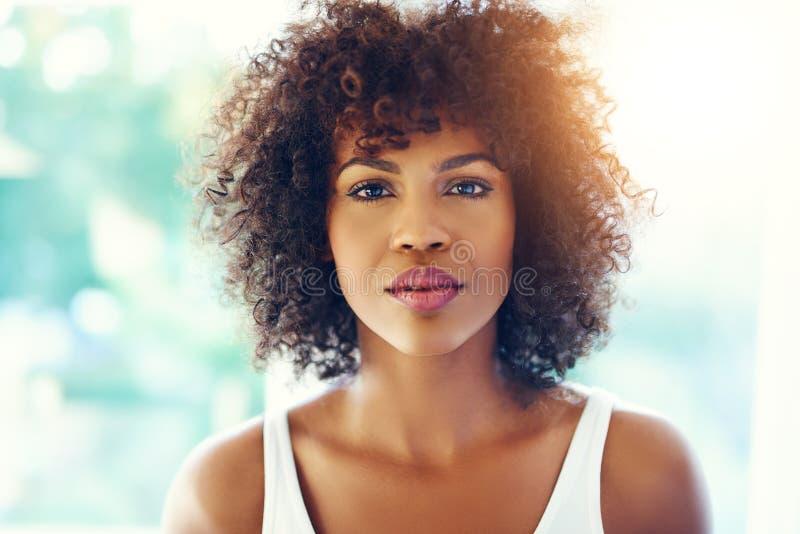 Mujer negra joven pensativa con la llamarada de la luz del sol fotografía de archivo