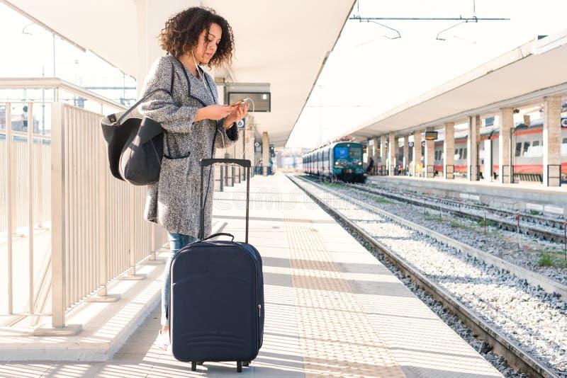 Mujer negra joven que espera el tren imagen de archivo libre de regalías