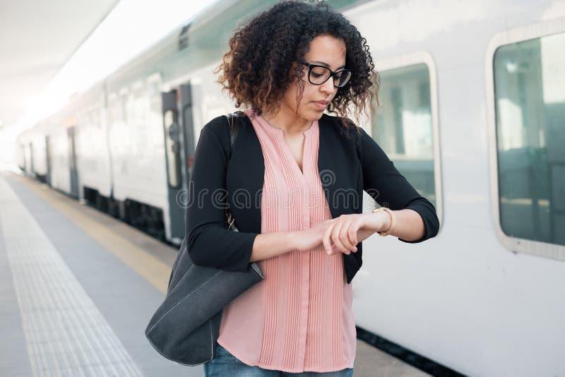 Mujer negra joven que espera el tren fotografía de archivo
