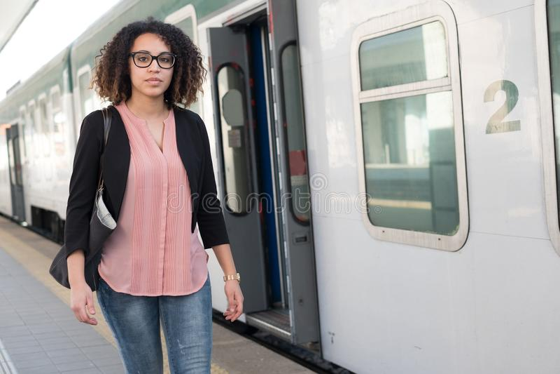 Mujer negra joven que espera el tren imagen de archivo