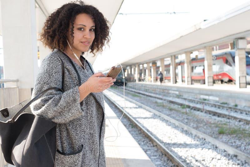 Mujer negra joven que espera el tren fotografía de archivo libre de regalías