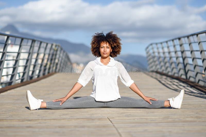 Mujer negra joven que hace estirar después de correr al aire libre fotografía de archivo
