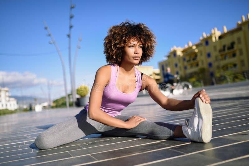 Mujer negra joven que hace estirar después de correr al aire libre fotos de archivo libres de regalías