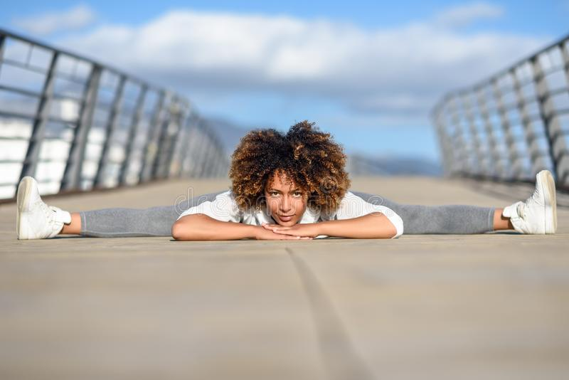 Mujer negra joven que hace estirar después de correr al aire libre foto de archivo