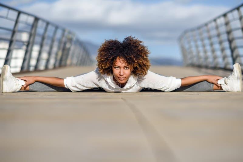 Mujer negra joven que hace estirar después de correr al aire libre fotos de archivo