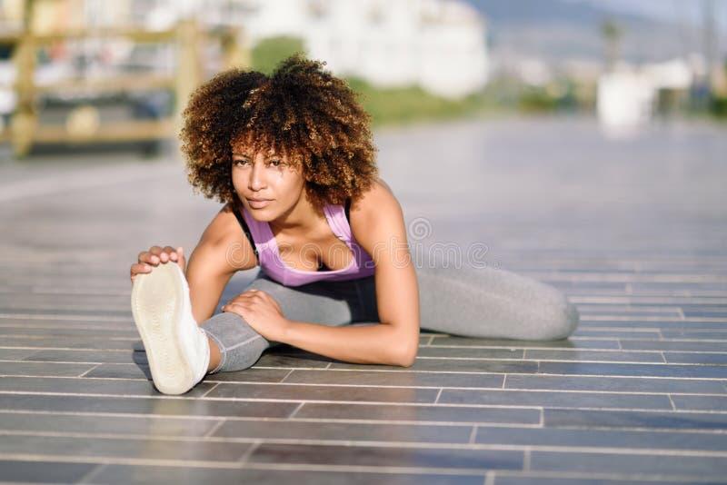 Mujer negra joven que hace estirar después de correr al aire libre imagen de archivo