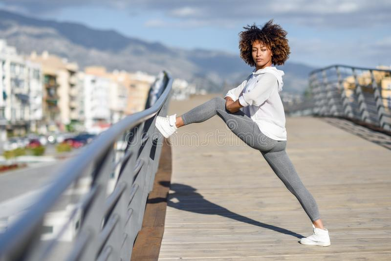 Mujer negra joven que hace estirar después de correr al aire libre imagenes de archivo