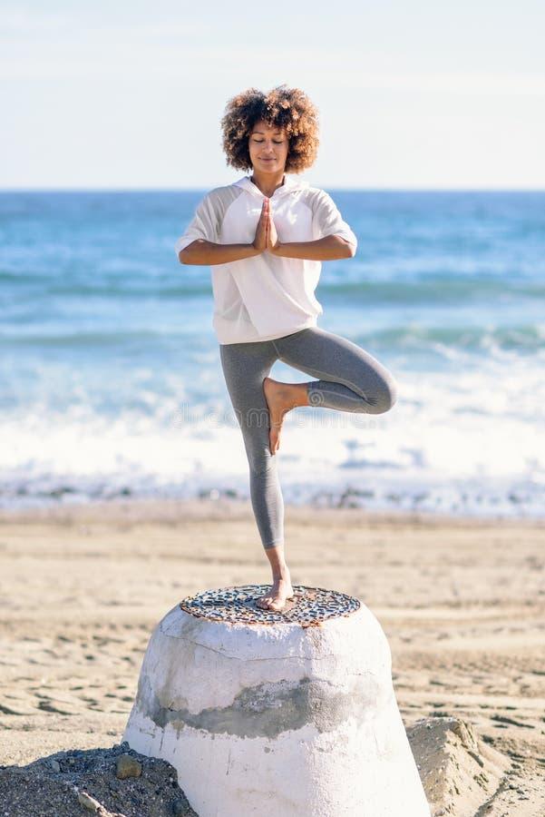 Mujer negra joven que hace yoga en la playa imagen de archivo