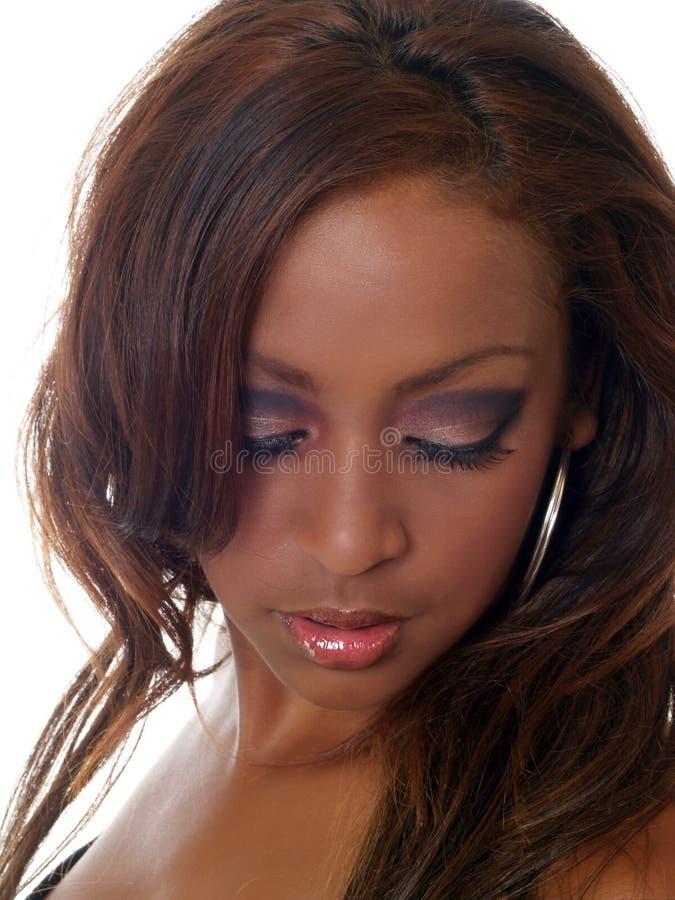 Mujer negra joven que mira abajo con maquillaje del ojo imagen de archivo libre de regalías