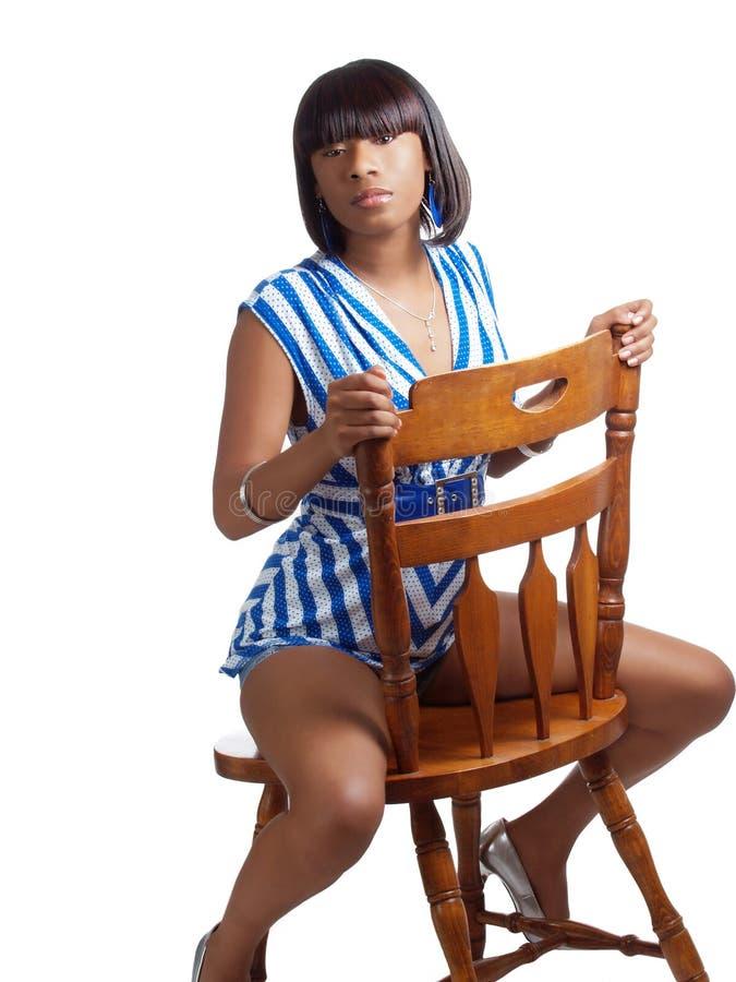 Mujer negra joven que monta la tapa de madera del azul a horcajadas de la silla fotos de archivo