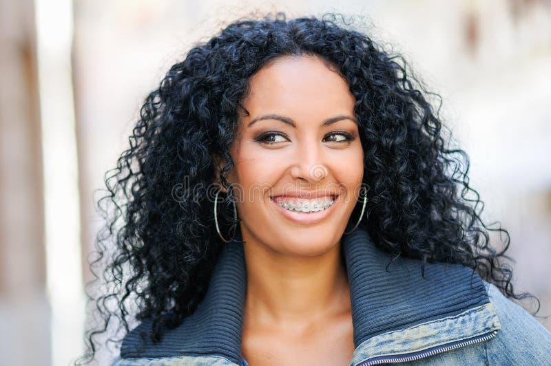 Mujer negra joven que sonríe con las paréntesis fotos de archivo