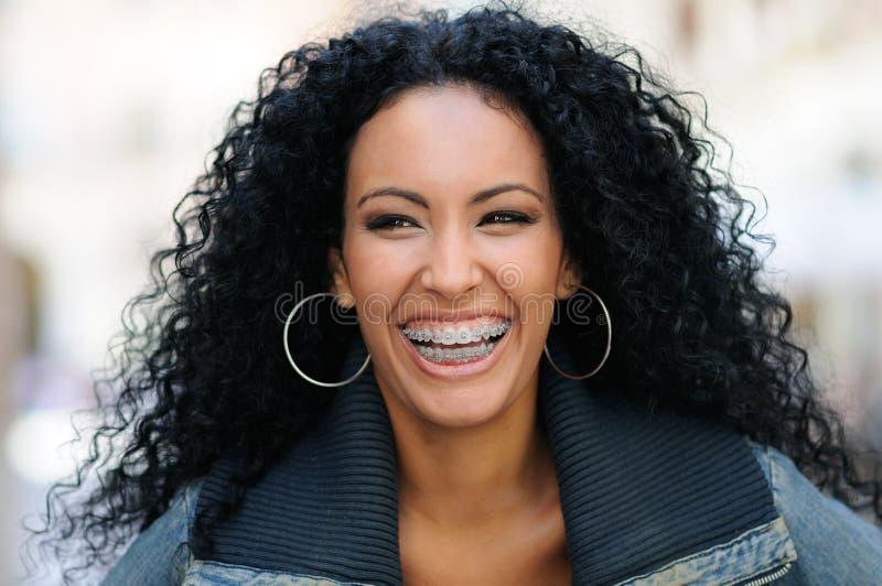 Mujer negra joven que sonríe con los apoyos imagenes de archivo