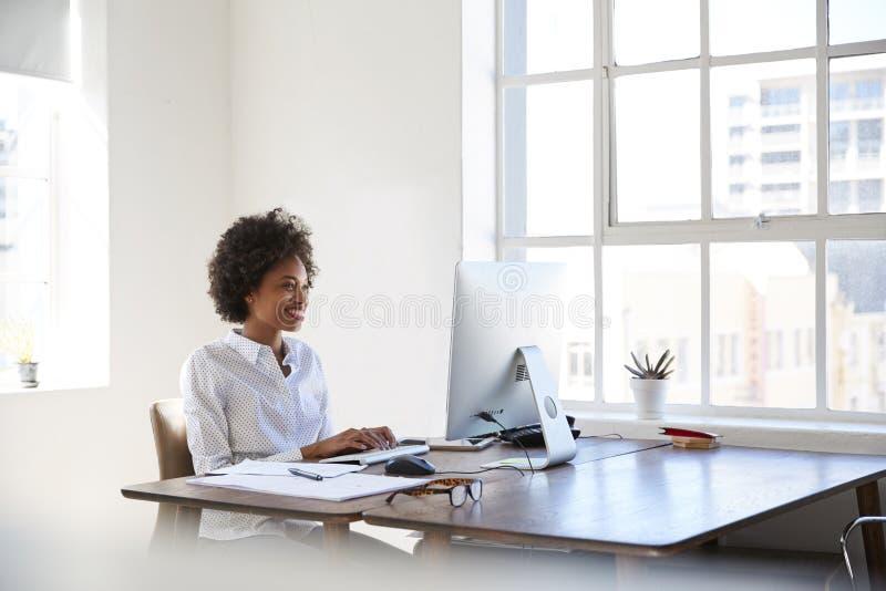 Mujer negra joven que trabaja en el ordenador en una oficina foto de archivo