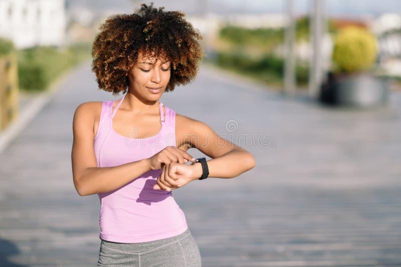Mujer negra joven que usa la pantalla táctil conmovedora del smartwatch imagenes de archivo