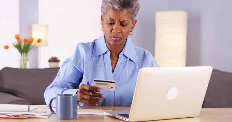 Mujer negra mayor que se sienta en piso con el equipo del ejercicio imagenes de archivo